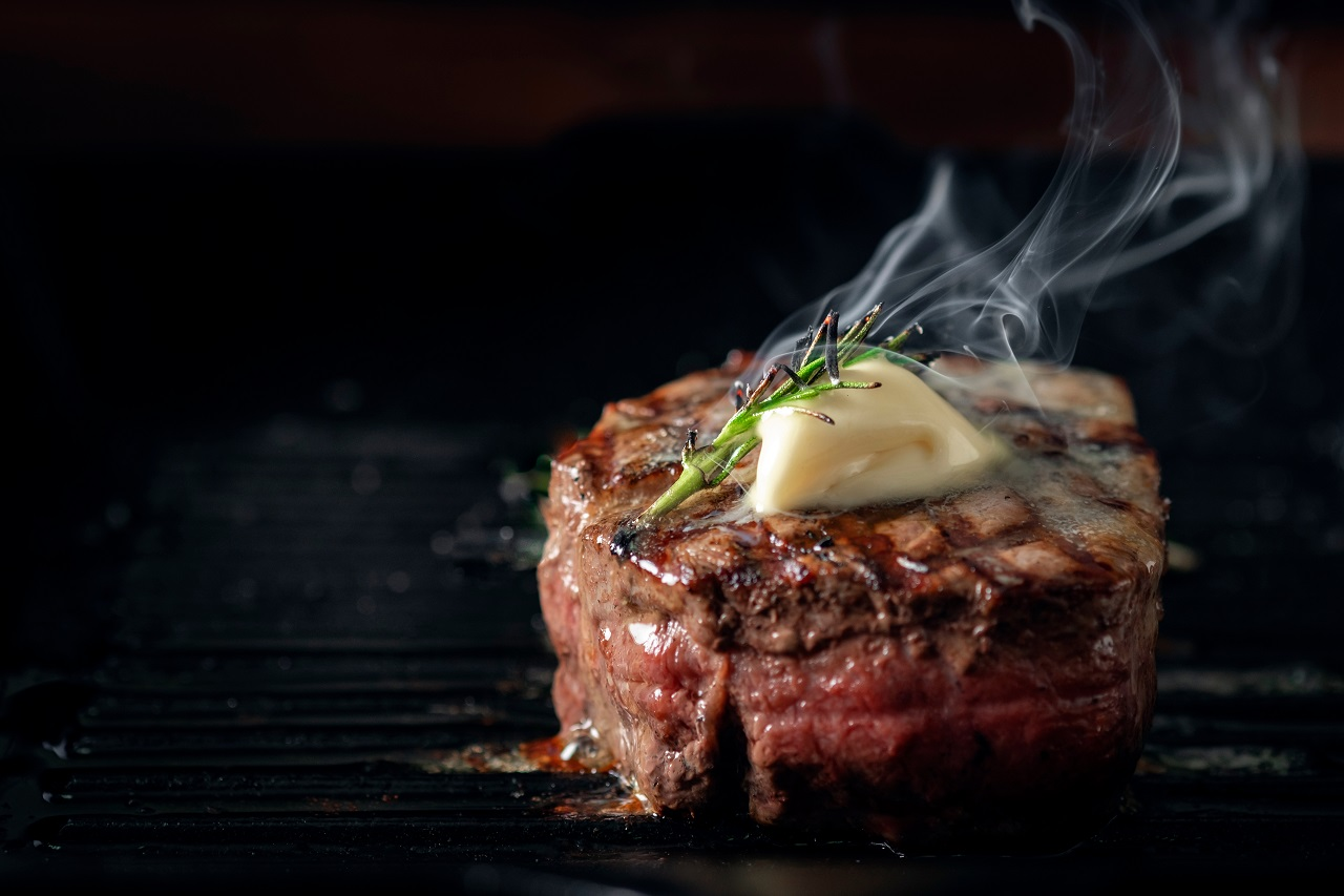 A-steaming-beef-tenderloin-steak-is-grilled-in-a-grill-pan-with-the-text-copy-space.-The-concept-of-the-recipe