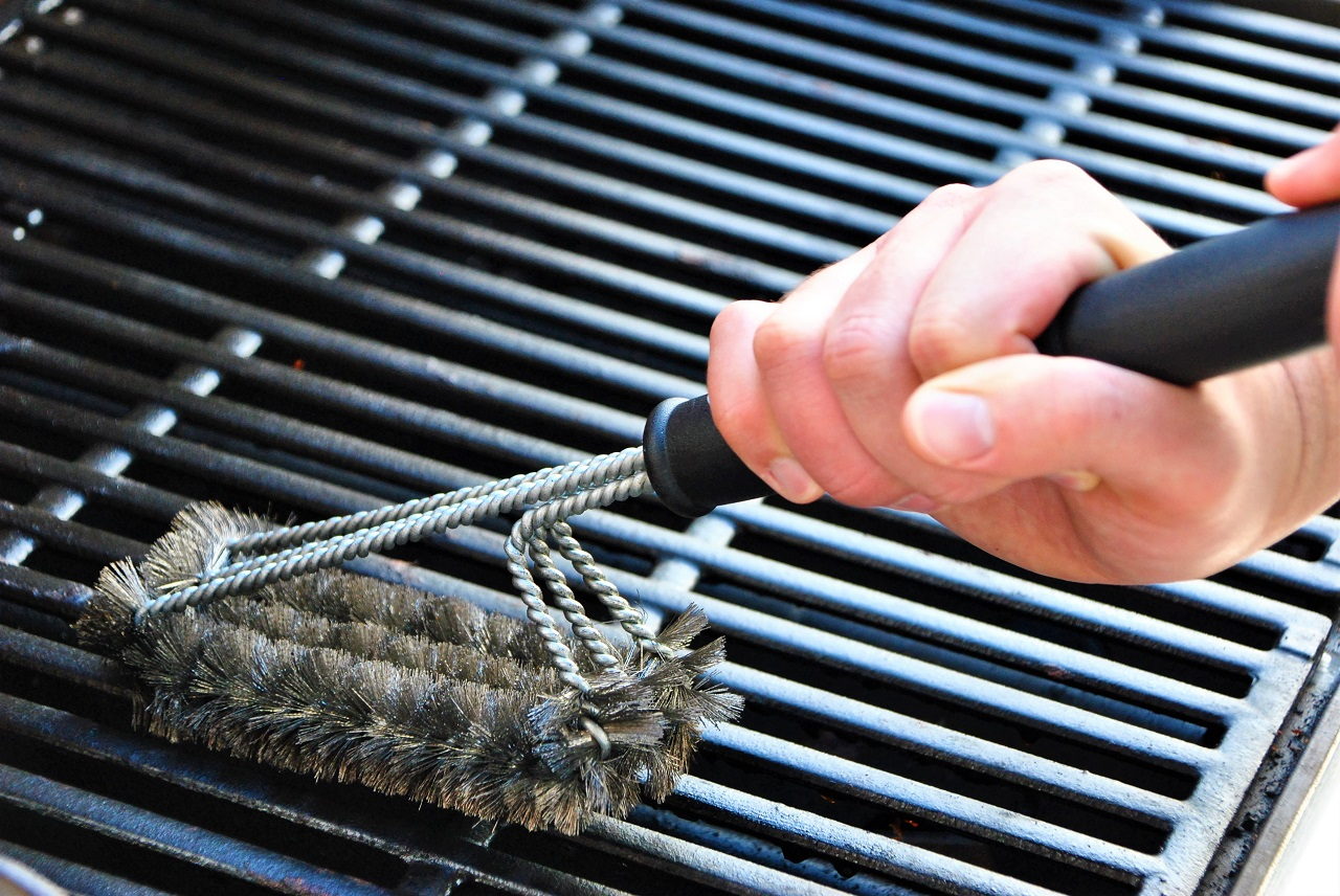 Cleaning-a-grill-at-a-summer-barbecue-party