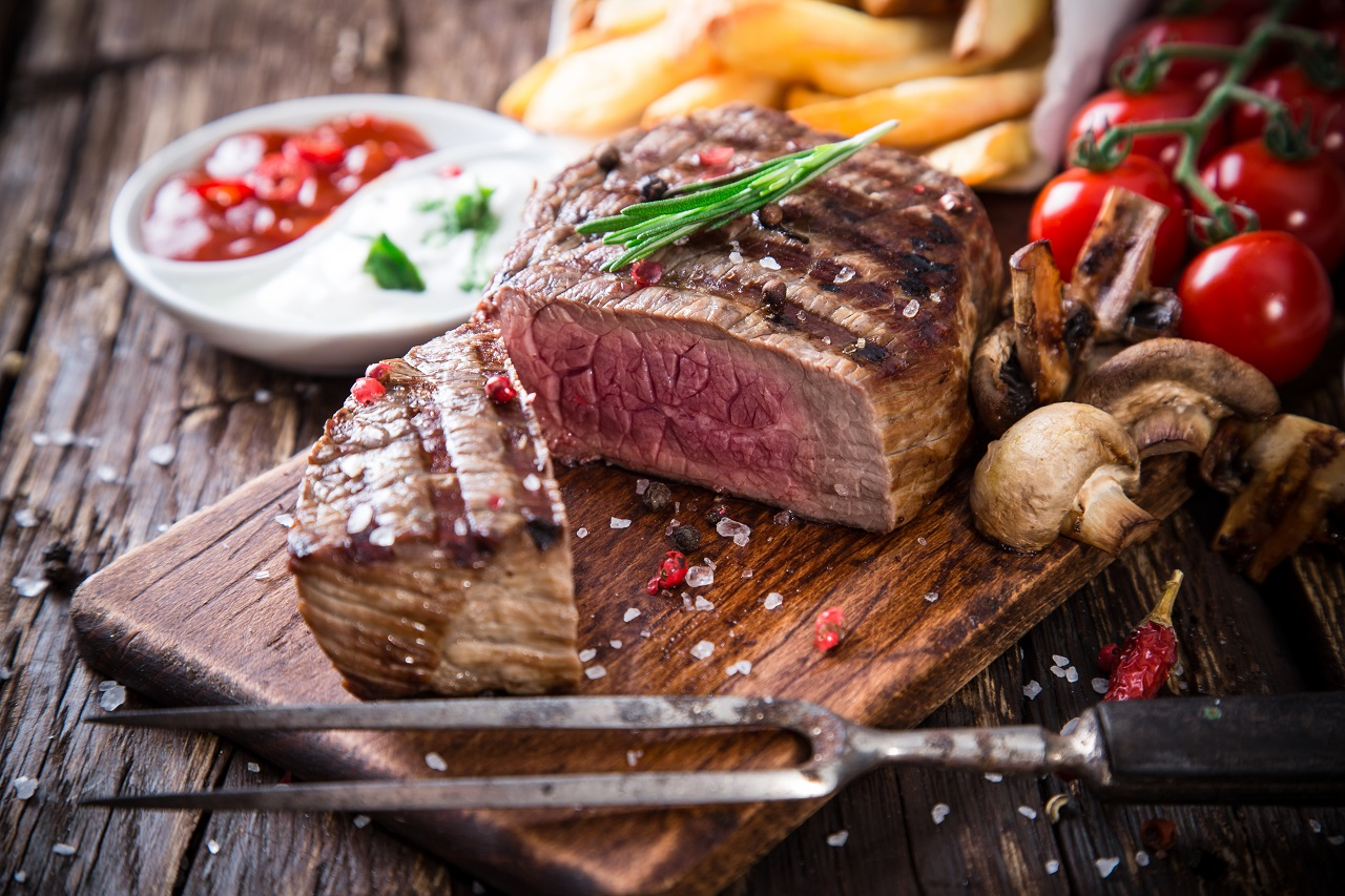 Delicious-beef-steak-on-wooden-table-close-up