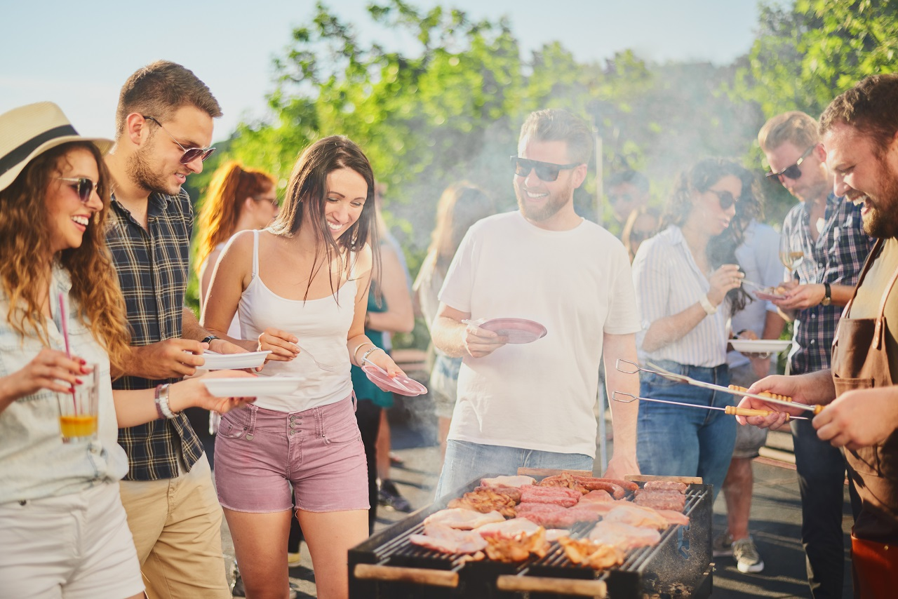 Group-of-people-standing-around-grill-chatting-drinking-and-eating