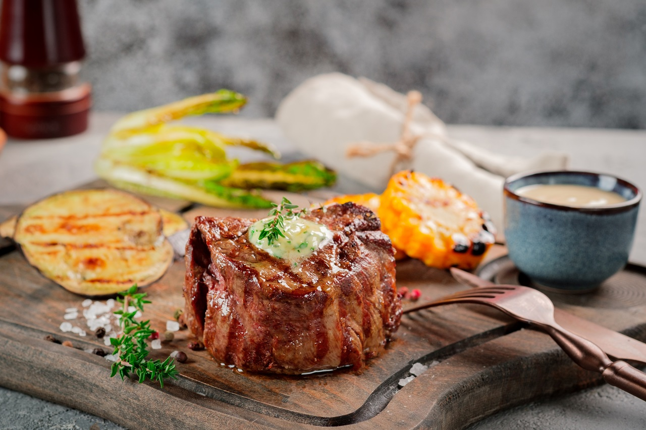 Large-grilled-Filet-Mignon-steak-with-butter-and-thyme-served-on-a-wooden-board.-Grilled-meat-dish-with-vegetables