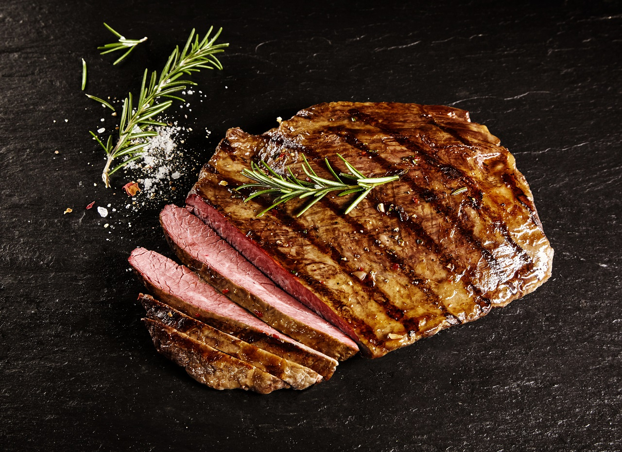 Single-roasted-medium-rare-sliced-flank-beef-piece-with-rosemary-over-dark-table-background