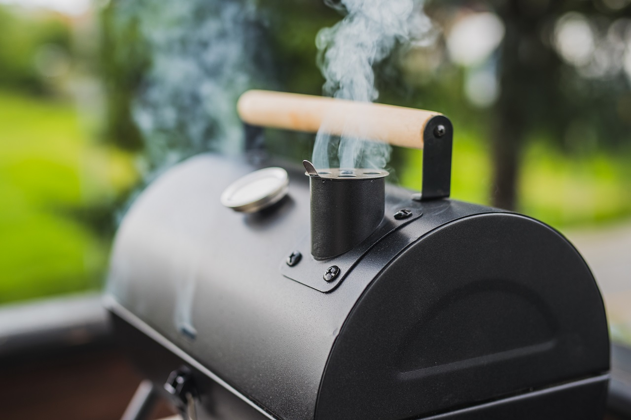 Smoke-coming-out-of-a-smokestack-of-a-small-black-smoker-grill-or-barbecue-on-green-background