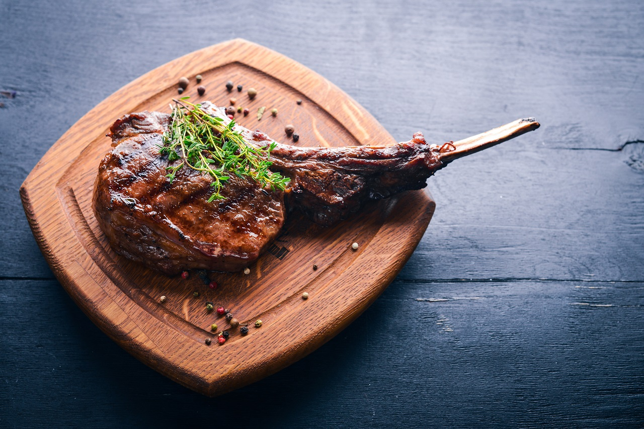 Steak-on-the-bone.-Top-view.-Free-space-for-text.-On-a-wooden-background