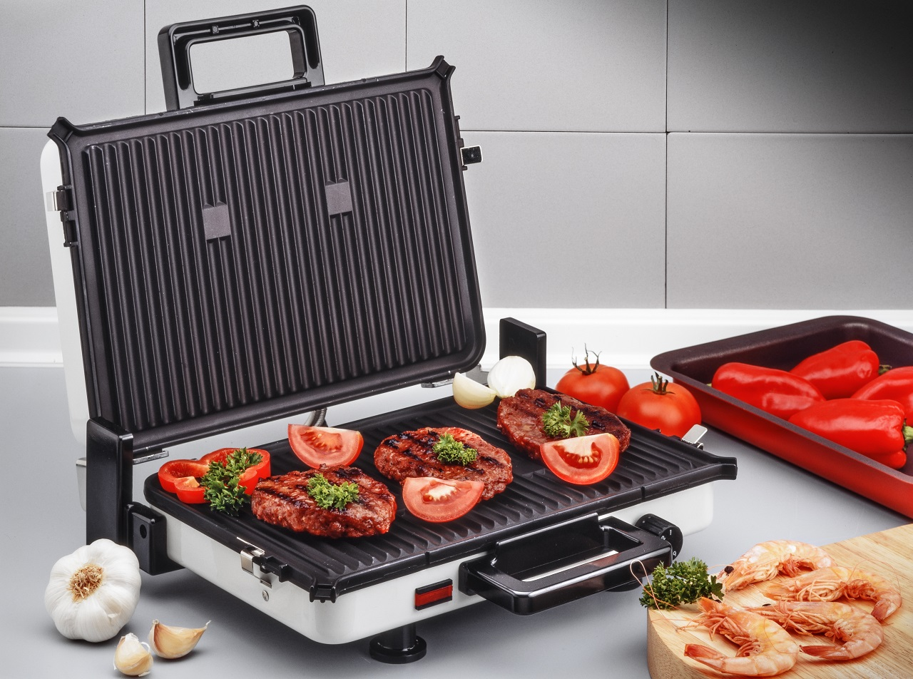 electric-grill-with-burgers-and-prawns-on-kitchen-board