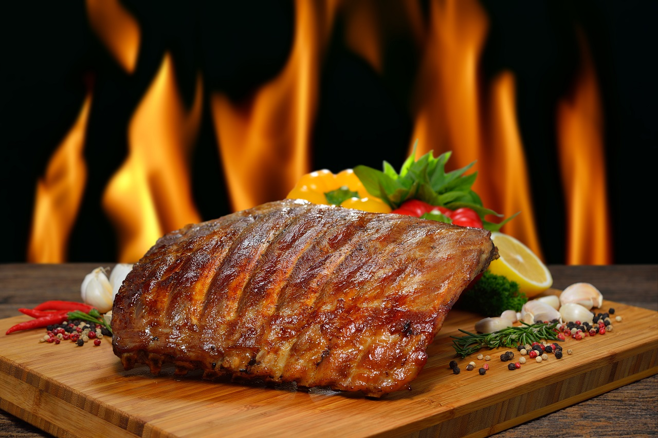 Grilled-pork-ribs-and-various-vegetables-on-a-chopping-wood